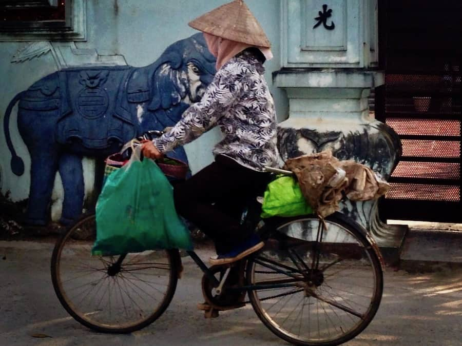 Woman cycling in Hanoi, Vietnam.