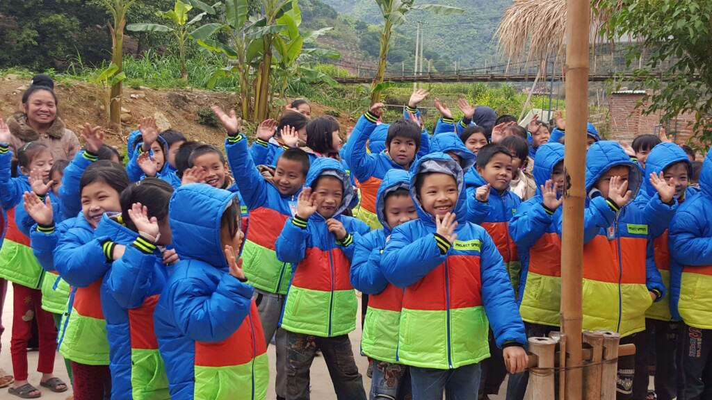 Children in Vietnam showing the new winter coats they received from Project Sprouts