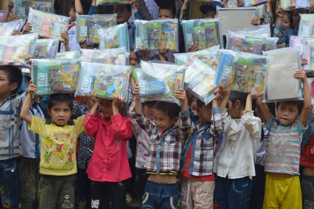 Children in Vietnam showing the school supplies they received from Project Sprouts