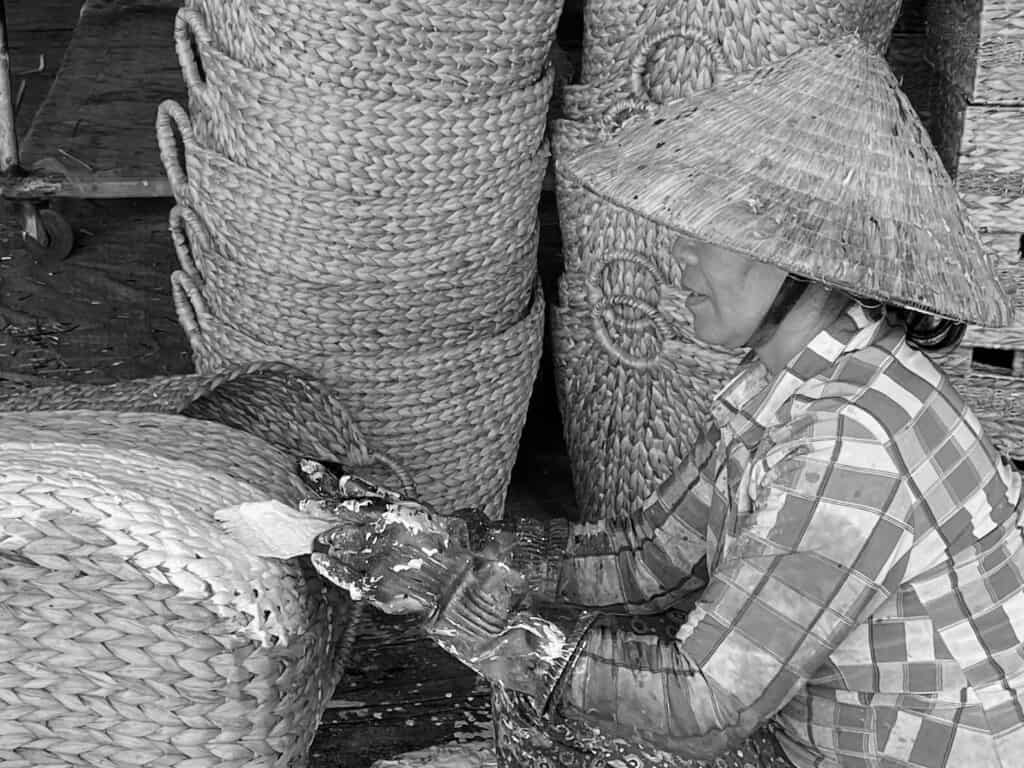 A Vietnamese artisan is painting a hand-woven basket.